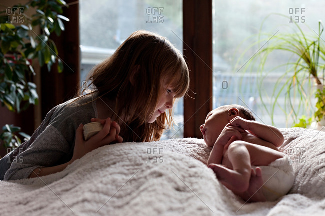 A little girl looks at her baby sister lovingly