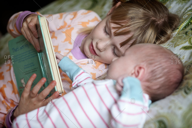 A girl reads her baby sister a story