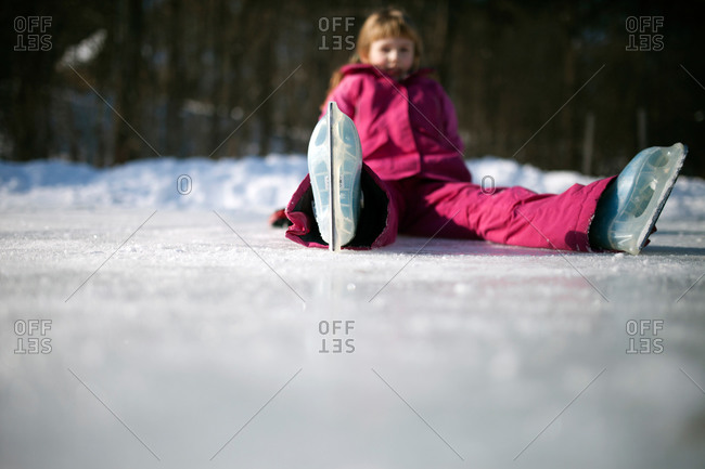 A little girl sits on ice in ice skates
