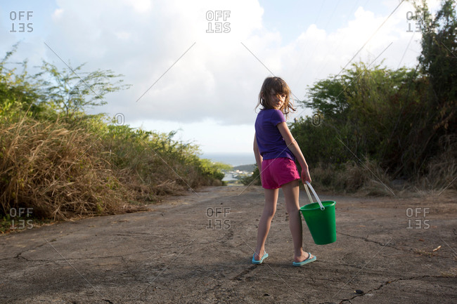 A little girl with a pail turns around