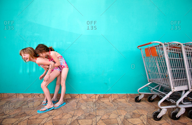 Two little girls in bathing suits play around next to a grocery store