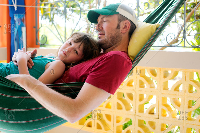 A dad holds his daughter on the hammock