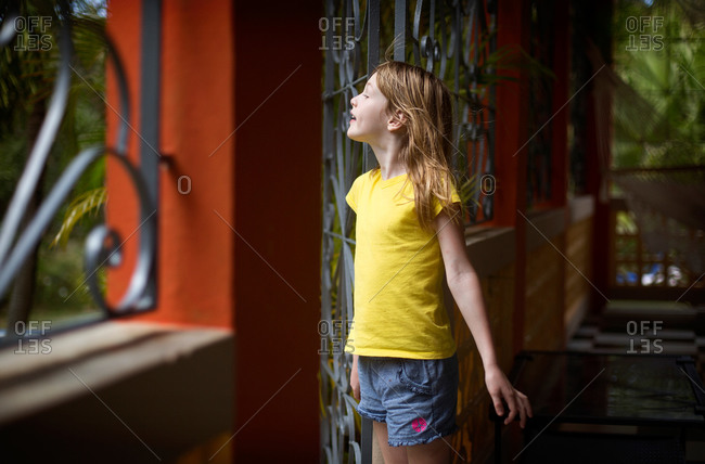 A little girl stands by a doorway and feels the breeze