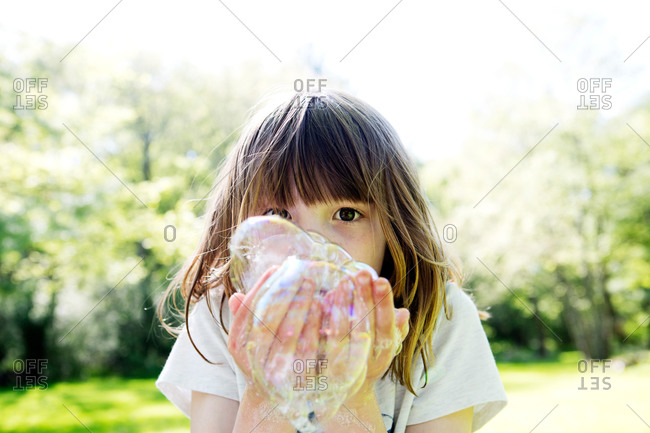 A little girl playing outside with bubbles