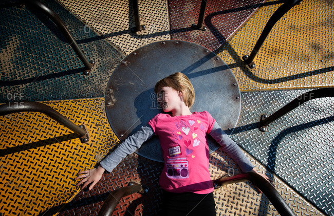 A girl lays on a playground roundabout