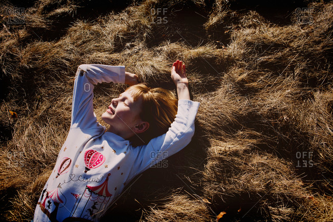 A little girl lays in brown grass