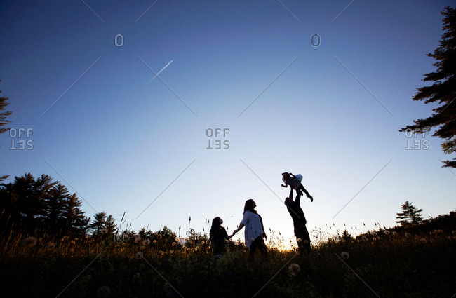 A family walks through a field at dusk