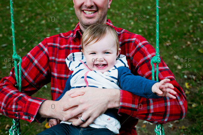 A baby girl on a swing with her dad