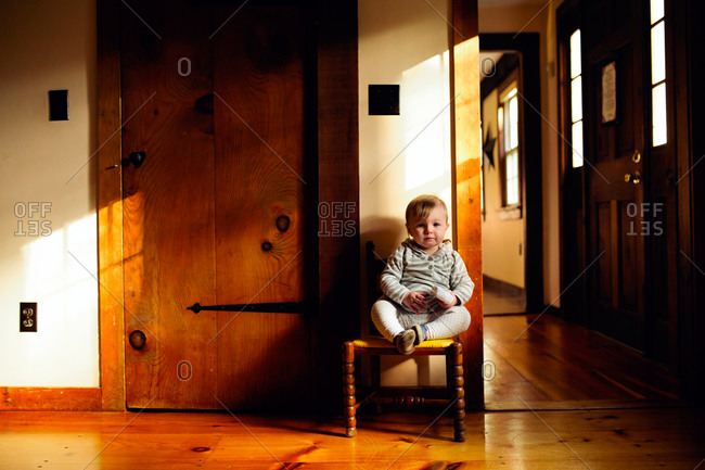 A little girl sits on a chair in a hallway