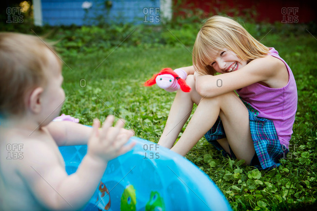 A little girl amuses her sister with a  sock puppet