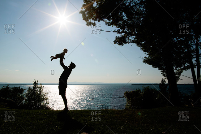 A father holds up his toddler by the edge of a lake