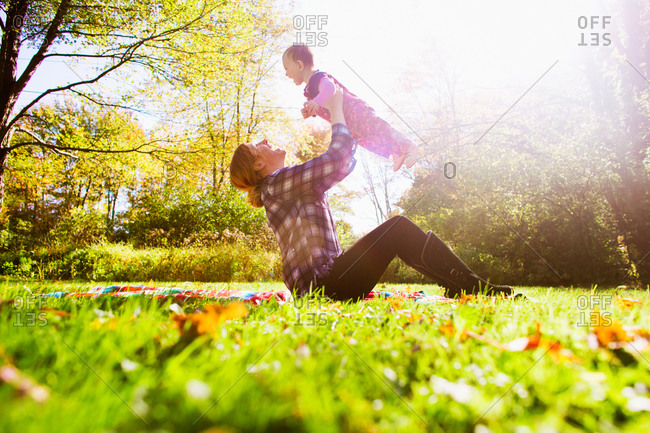 A mother lifts her baby girl up in a park