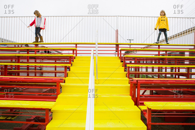 Two girls stand on colorful bleachers