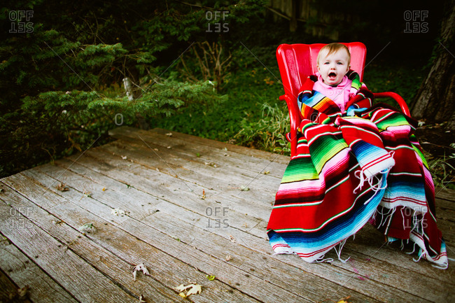A baby wrapped in a colorful blanket sits on a porch