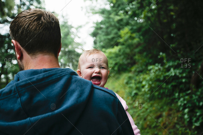 A father carries his baby down a forest path