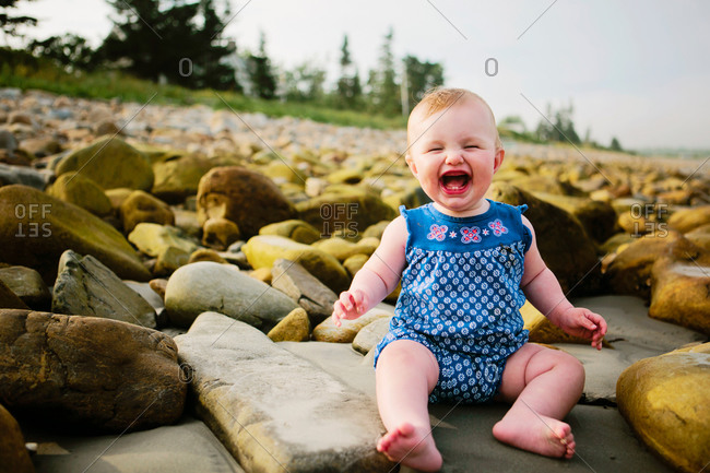 A baby laughs joyfully on a rocky beach
