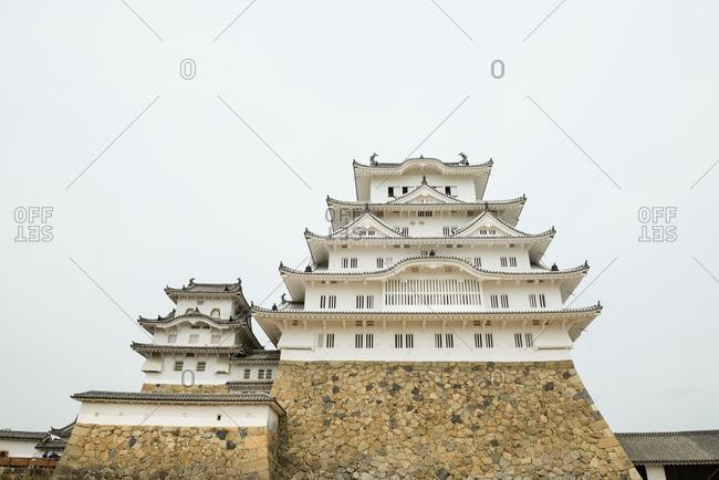 Hyougoken, Japan - April 11, 2015: Himeji castle perched on top of a stone wall in Hyoukoken, Japan