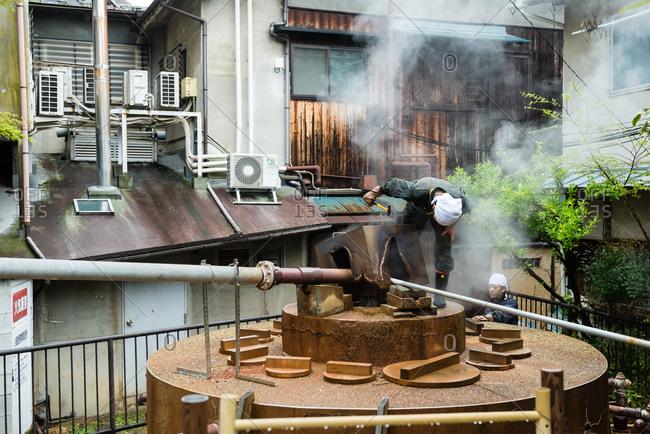 Kobe, Japan - April 13, 2015: Women check on an outdoors kiln