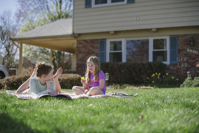 Two girls laying on blanket in front yard