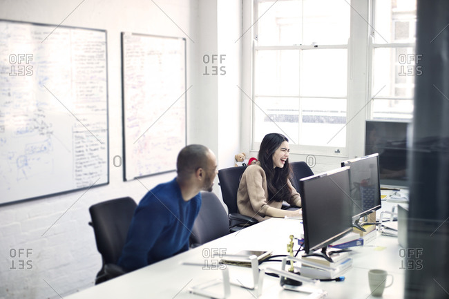Colleagues at their desks in office smiling