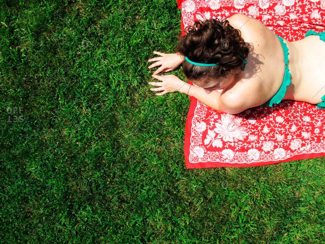 Woman lying on blanket on grass in bikini