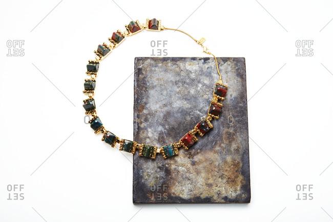 Necklace and stone slab on white background