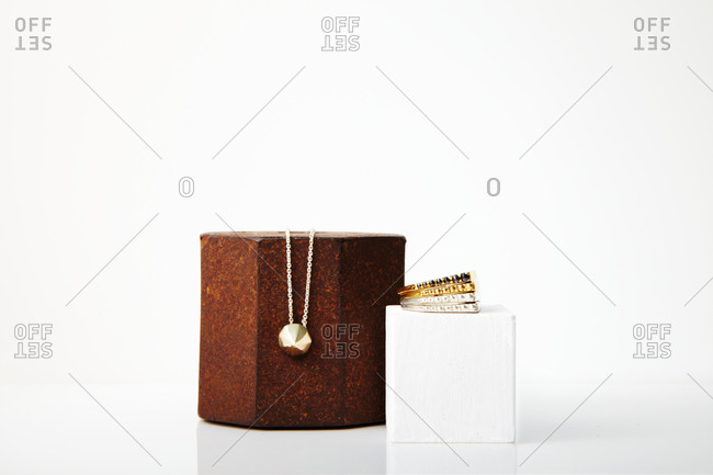 Jewelry and hexagonal stone on white background