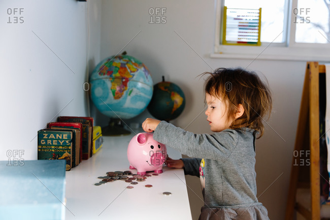 Little girl putting money in her piggy bank