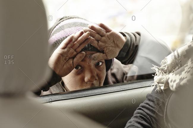 Kathmandu, Nepal - February 12, 2013: Young beggar in Kathmandu, Nepal peering through car window
