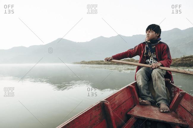 Pokhara, Nepal - February 11, 2013: Young boy paddling canoe on lake in Pokhara, Nepal