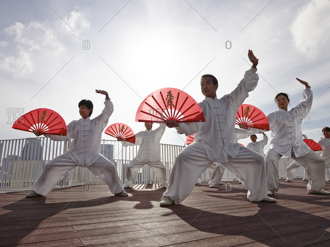Singapore - February 7, 2013: Fan dancers in unison on a rooftop in Singapore