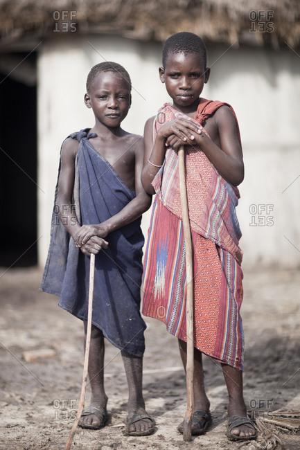 Tarangire, Tanzania - January 8, 2010: Young Maasai village boys with sticks ready to herd goats