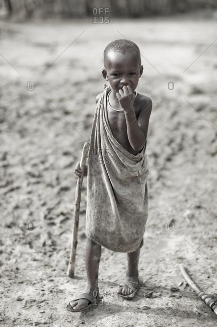 Tarangire, Tanzania - January 8, 2010: Young Maasai village boy with stick in Tarangire, Tanzania