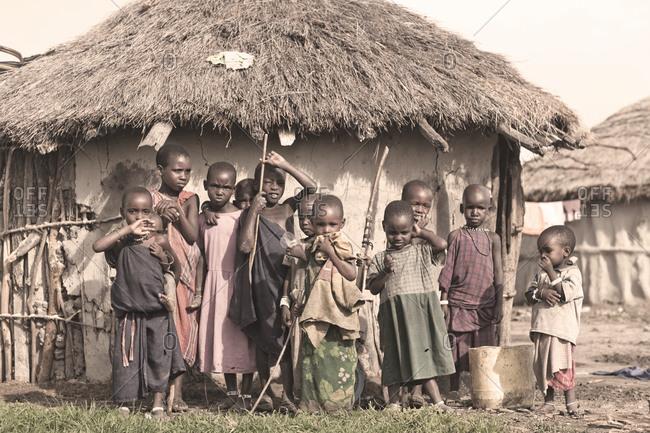 Tarangire, Tanzania - January 8, 2010: Maasai village children in front of traditional hut, Tarangire, Tanzania