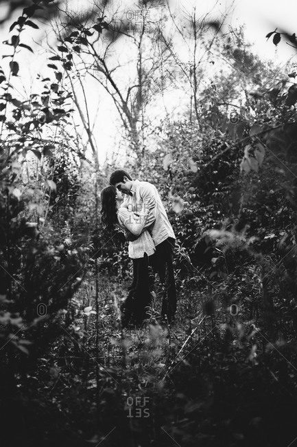 Romantic couple share an intimate moment in the woods
