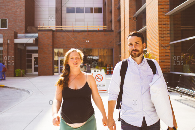 A husband and his pregnant wife walk towards a hospital