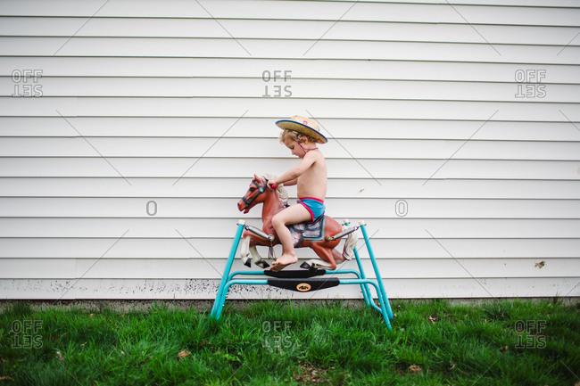 Shirtless little boy riding a spring horse in backyard