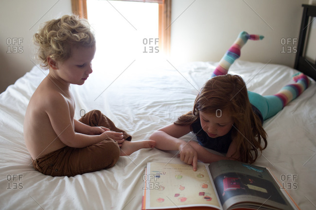 Girl reading to her brother while lying on a bed