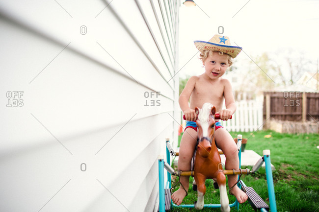 Happy little boy riding a spring horse outside