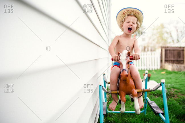 Little boy playing cowboy rides a spring horse outside