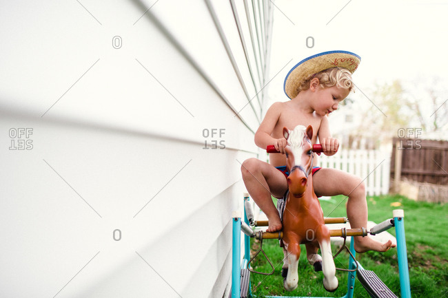 Child riding a spring horse up against the outside of his house