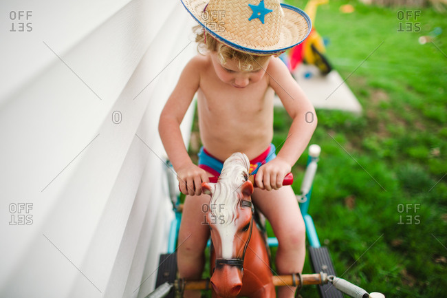 Little boy in cowboy hat riding a spring horse