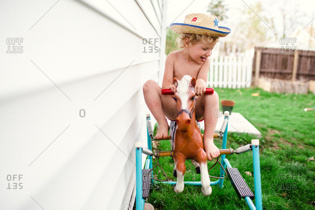 Little boy wearing a cowboy hat rides a hobby horse in his yard
