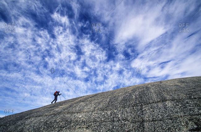 Hiker ascends dome in Tuolumne Meadows, Yosemite National Park