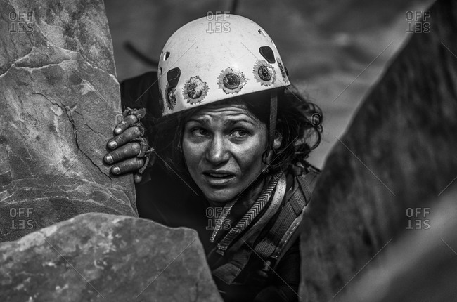Climber scopes her next move on challenging cliff