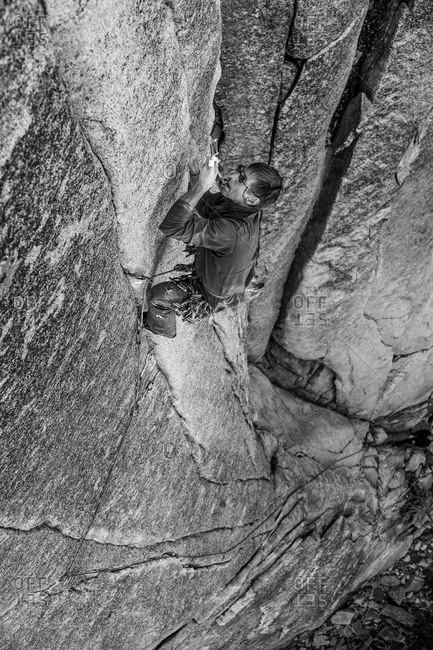 Climber struggles up a challenging cliff