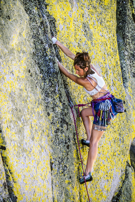 Climber gripping edge of challenging cliff