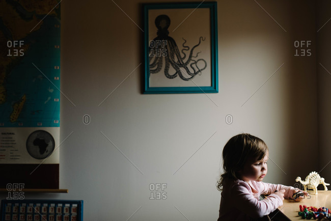 Young girl holding a cookie at a table