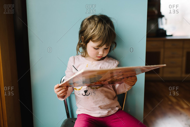 Young girl holding a book on a chair