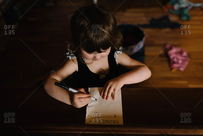 Young girl writing on a paper